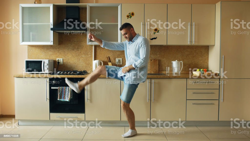 Handsome young funny man dancing in kitchen at home in the morning and have fun on holidays stock photo