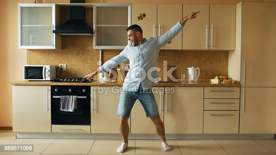 istock Handsome young funny man dancing in kitchen at home in the morning and have fun on holidays 889571058
