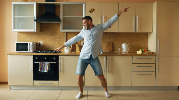 handsome young funny man dancing in kitchen at home in the morning and have fun on holidays - tipo di danza foto e immagini stock