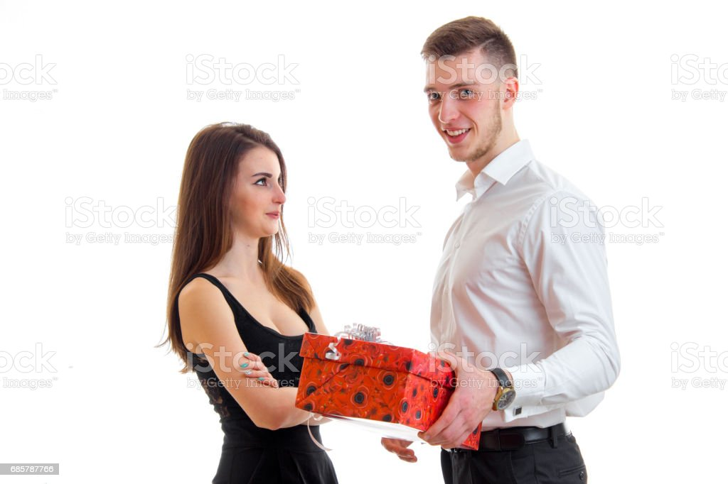 handsome young guy gives his girlfriend a big red gift stock photo