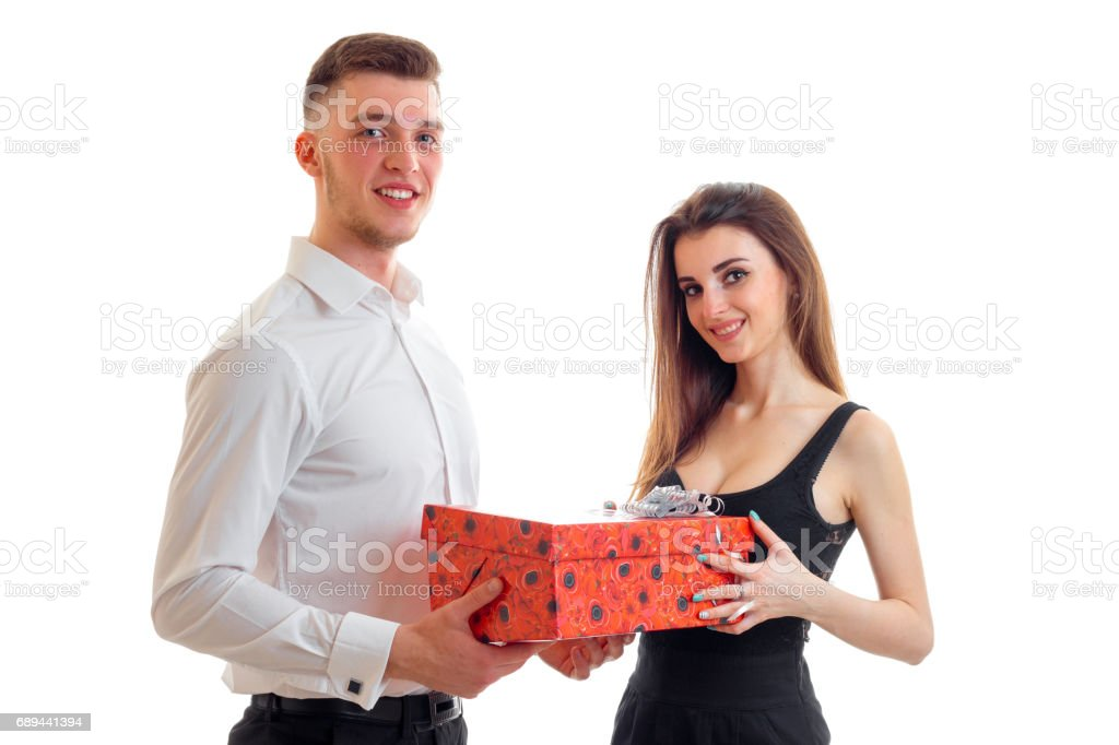 handsome young guy in a shirt with a charming girl and they are holding a gift stock photo