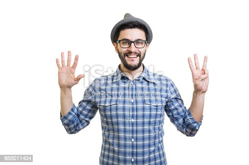 636829300 istock photo Handsome young guy in eyeglasses and hat showing eight on hand 855011404