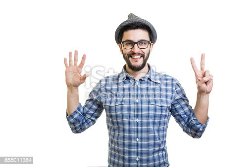 636829300 istock photo Handsome young guy in eyeglasses and hat showing seven on hand 855011384