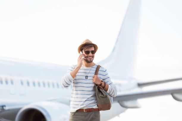 Hübscher junger Mann vor einem Flugzeug – Foto