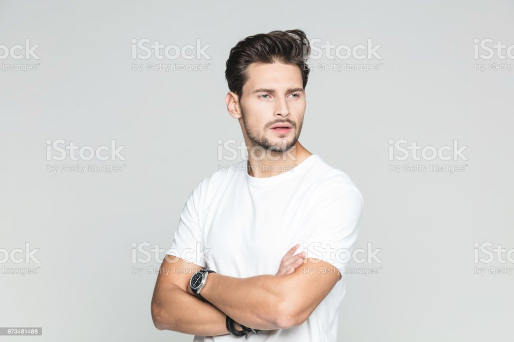 Handsome young guy looking at copy space Portrait of handsome young man standing with his arms crossed and looking away on grey background 25-29 Years Stock Photo