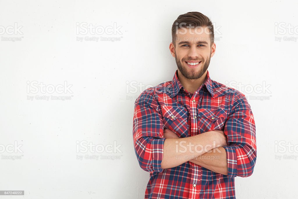 Handsome young guy standing against white wall. stock photo