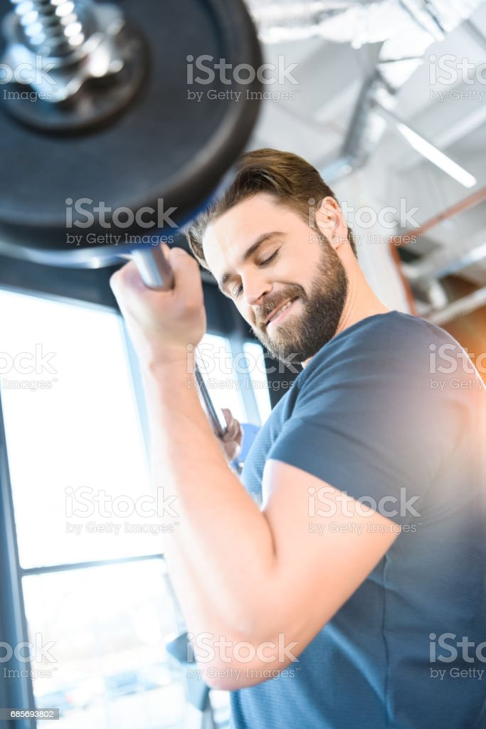 Handsome young guy workout with barbell 免版稅 stock photo