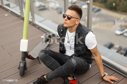 Handsome young hipster man in a vintage denim vest in gray jeans in sneakers in sunglasses rest on a wooden floor on the summer terrace after a ride on an electric scooter.Stylish guy relaxes outdoors