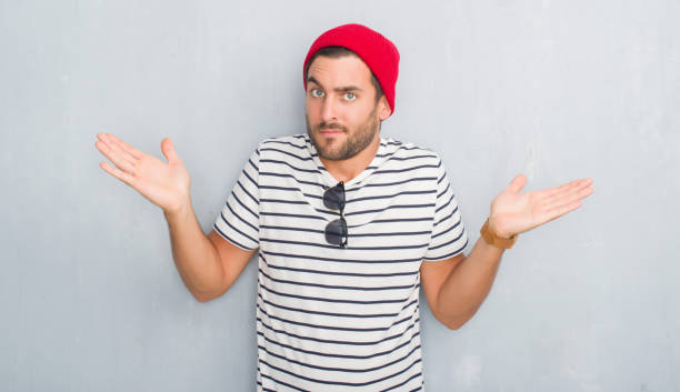 Handsome young hipster man over grey grunge wall wearing navy t-shirt and wool cap clueless and confused expression with arms and hands raised. Doubt concept. Handsome young hipster man over grey grunge wall wearing navy t-shirt and wool cap clueless and confused expression with arms and hands raised. Doubt concept. shrugging stock pictures, royalty-free photos & images