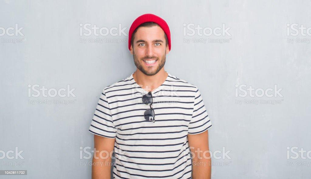 Yakışıklı genç hipster adam yüzünde lacivert t-shirt ve mutlu ve güzel bir gülümseme ile Yün şapka giyen gri grunge duvarın üzerinden. Şanslı kişi. stok fotoğrafı