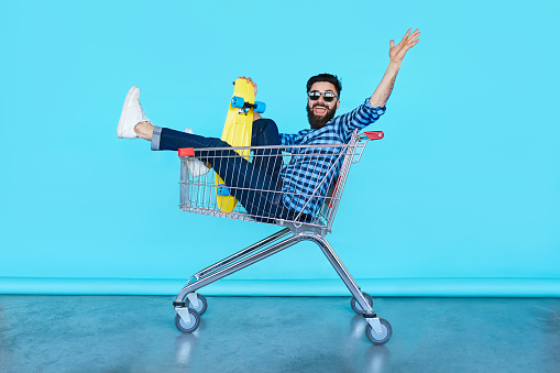 handsome young hipster man sitting in the shopping cart