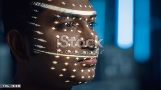 istock Handsome Young Indian Man is Identified by Biometric Facial Recognition Scanning Process. Futuristic Concept: Projector Identifies Individual by Illuminating Face by Dots and Scanning with Laser 1197070994