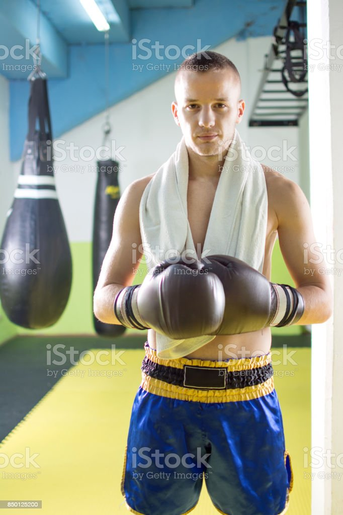 Handsome young kick boxer with boxing gloves and towel around his neck in exercise hall. stock photo