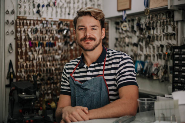 Guapo joven cerrajero posando en su tienda familiar - foto de stock