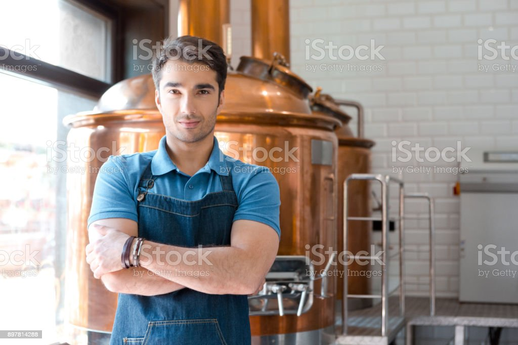 Handsome young male bartender standing in microbrewery Portrait of handsome young male bartender standing with crossed arms in microbrewery. Master brewer in uniform looking at camera. Adult Stock Photo