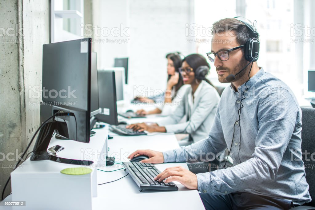 Handsome young male customer support executive working in office. stock photo