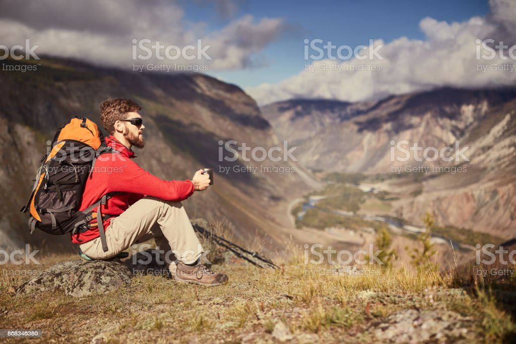 Handsome young male hiker sitting on the edge of a canyon looking away stock photo