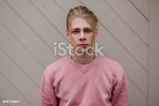 846124694 istock photo Handsome young male model in a pink fashion sweater near a wooden wall 846126924