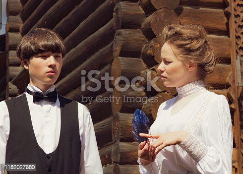 istock Handsome young man and girl dressed in the style of the 19th century. Human relations, brother and sister talk. Historical reenactment 1182027680