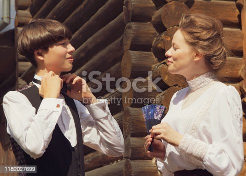 istock Handsome young man and girl dressed in the style of the 19th century. Human relations, brother and sister talk. Historical reenactment 1182027699
