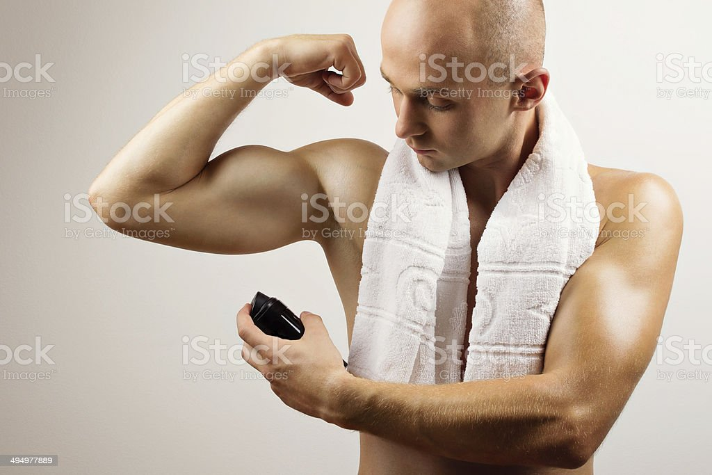 Handsome young man applying antiperspirant deodorant stock photo