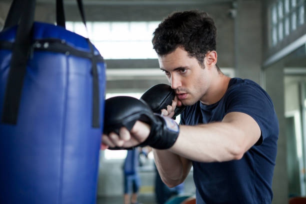 Handsome young man boxer is exercising with a punching bag at training fitness gym.male boxing workout sports stock photo