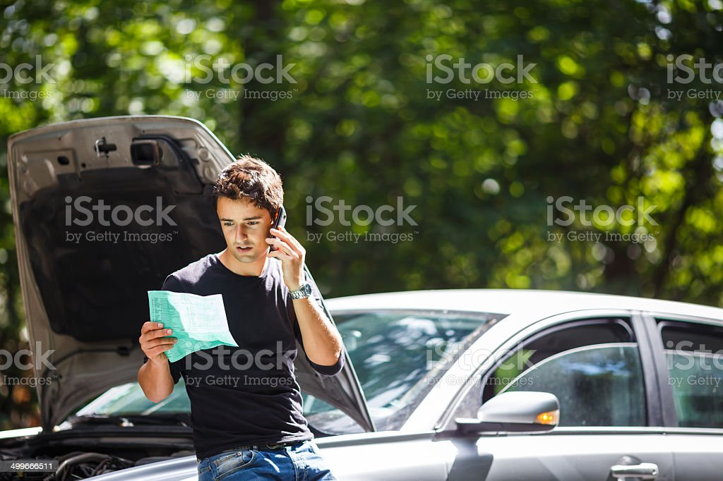 Handsome young man calling for roadside assistance stock photo