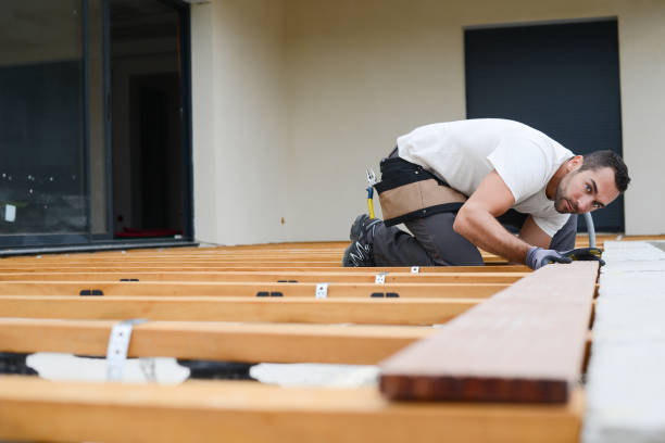 handsome young man carpenter installing a wood floor outdoor terrace in new house construction site - installare foto e immagini stock