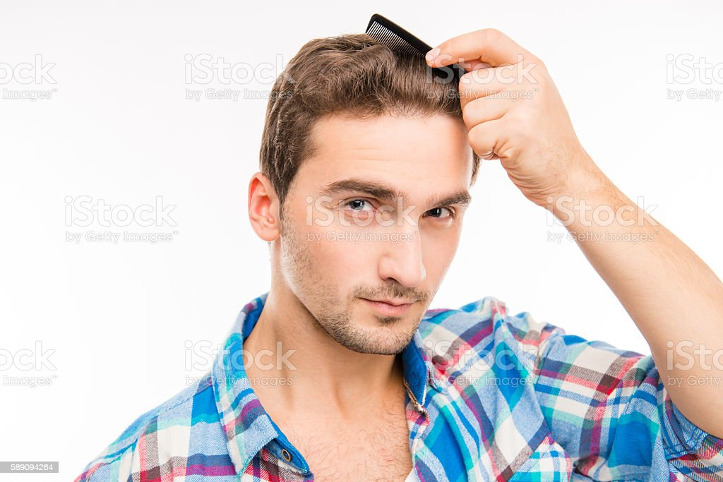 Handsome young man combing his hair stock photo