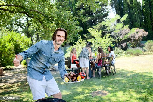 istock handsome young man cooking meat in barbecue party outdoor in the garden during summer holiday 823390192