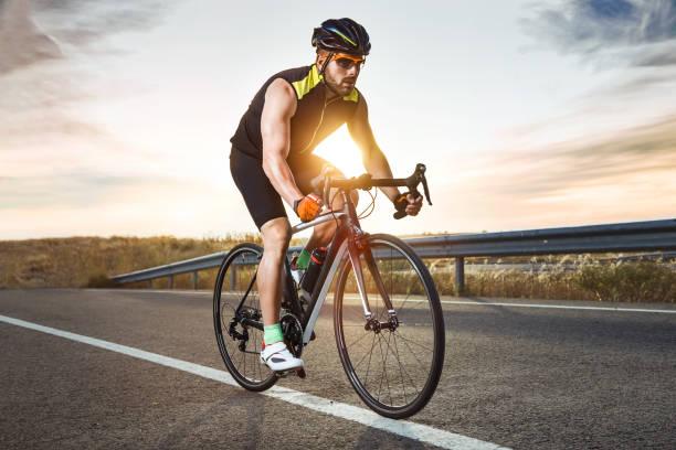 bel giovanotto in bicicletta sulla strada. - ciclismo foto e immagini stock
