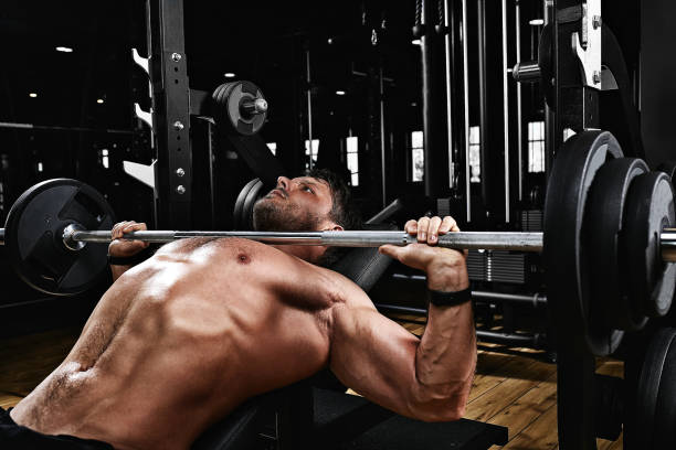 handsome young man doing bench press workout in gym, Fitness motivation, sports lifestyle, health, athletic body, body positive. Film grain, selective focus stock photo