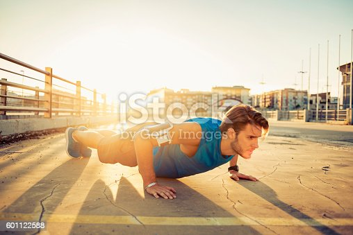 519676858istockphoto handsome young man doing push ups 601122588