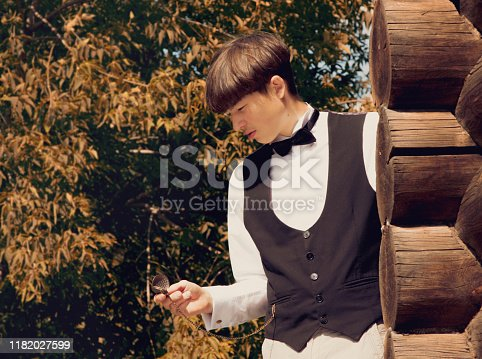 istock Handsome young man dressed in 19th century style. He stands near wall of a wooden house and looks at watch on a chain. Historical reenactment 1182027599