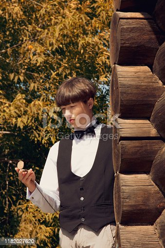 istock Handsome young man dressed in 19th century style. He stands near wall of a wooden house and looks at watch on a chain. Historical reenactment 1182027620