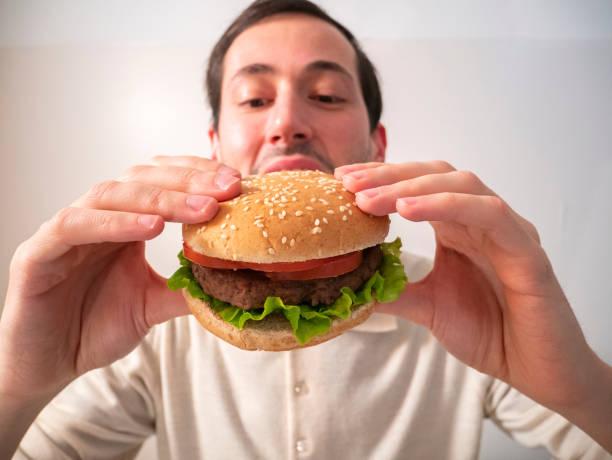 Handsome young man eating tasty hamburger stock photo
