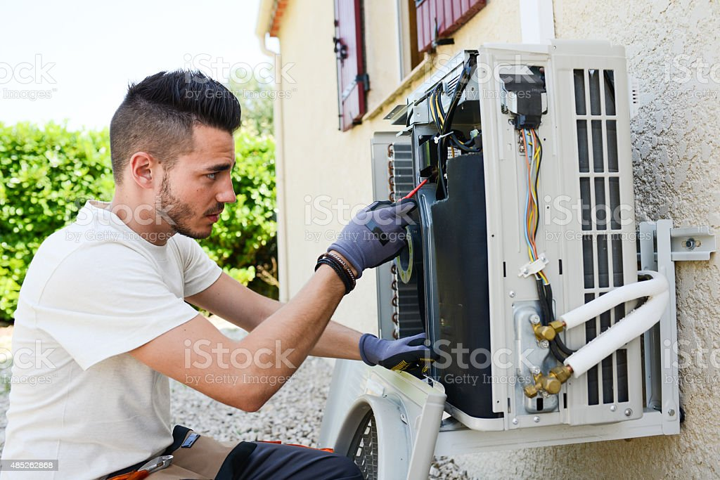 handsome young man electrician installing air conditioning in client house stock photo