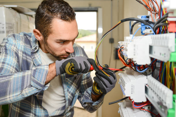 handsome young man electrician working on switchboard of house building construction site - fuse box stock photos and pictures