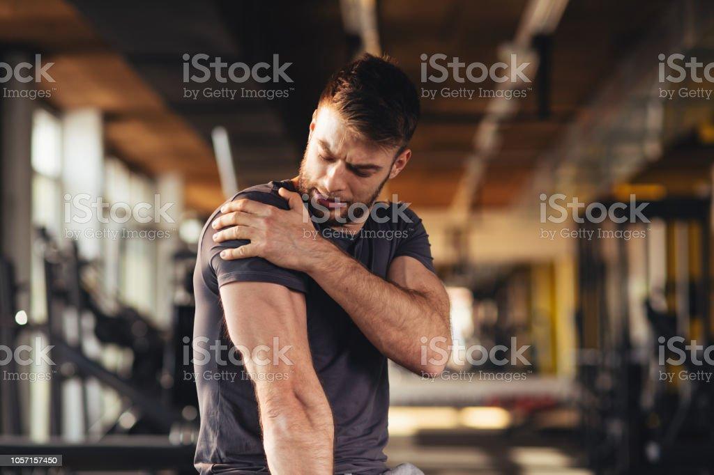 Hübscher junger Mann fühlen den Schmerz in der Schulter in der Turnhalle – Foto