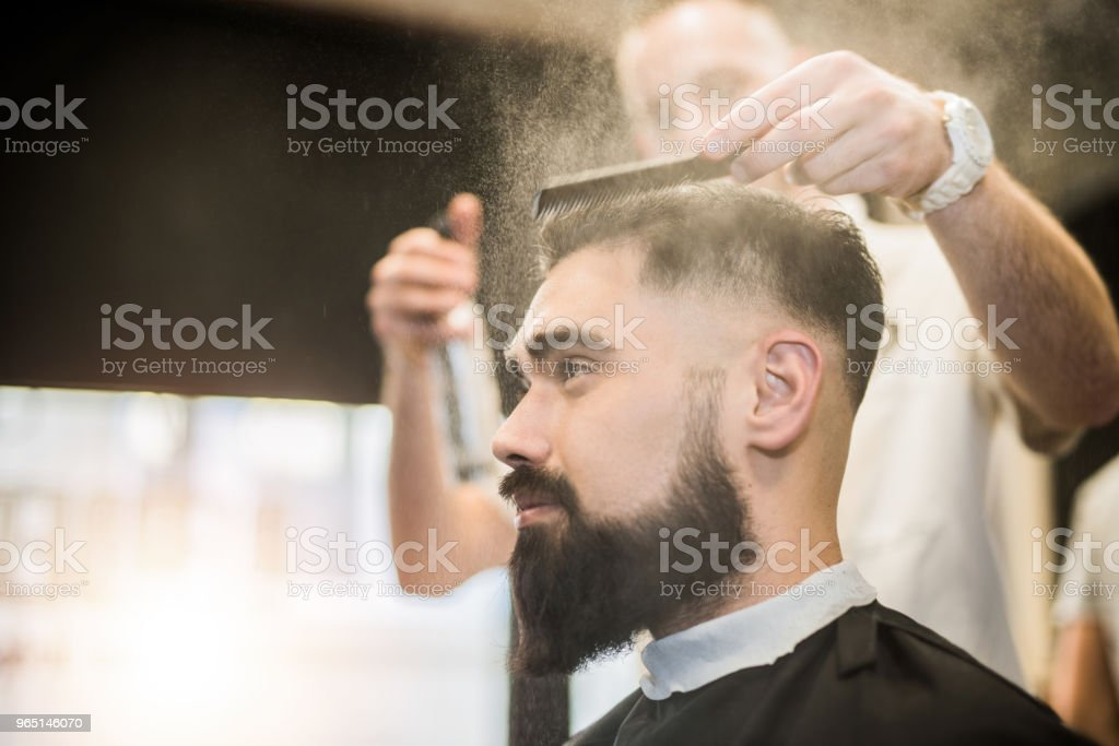 Handsome young man getting a haircut. zbiór zdjęć royalty-free