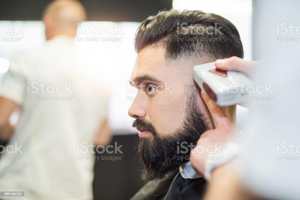 Handsome young man getting a haircut profile view. zbiór zdjęć royalty-free