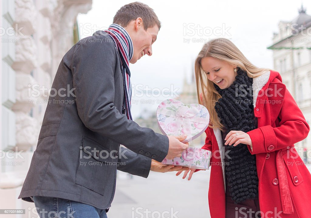 Handsome Young Man Giving His Girlfriend a Gift Box stock photo