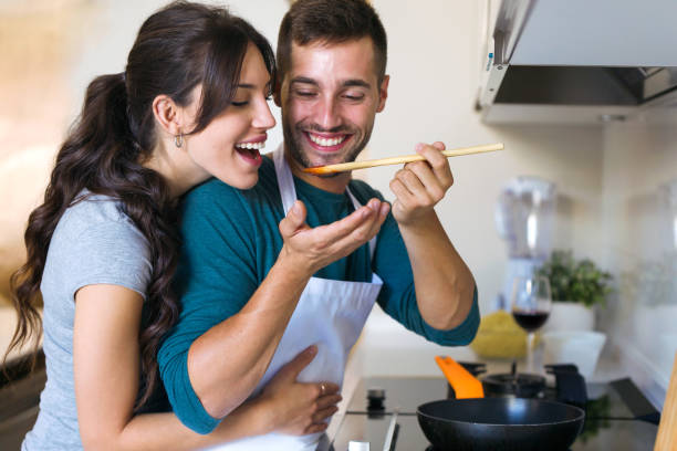 Handsome young man giving his wife to try the food he is preparing in the kitchen at home. Shot of handsome young man giving his wife to try the food he is preparing in the kitchen at home. romance stock pictures, royalty-free photos & images