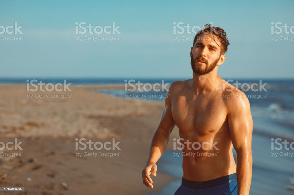 Handsome young man having fun on the beach by the sea stock photo
