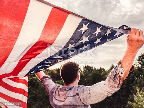 Attractive man in jeans and denim shirt holding an American Flag on a cloudy sky background. Bottom view, close-up. National holiday concept