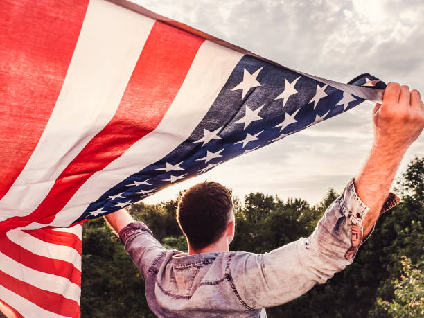Handsome, young man holding an American flag stock photo