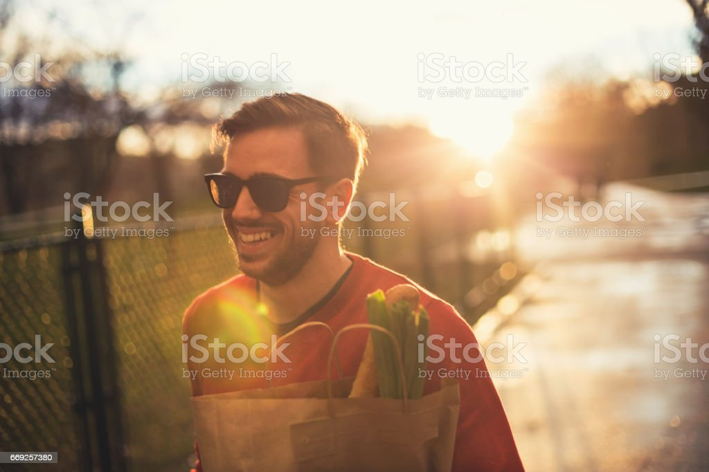 Handsome young man holding grocery bag stock photo