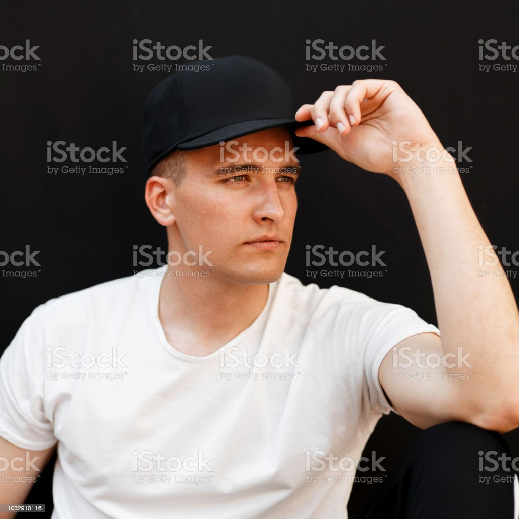 8b5867bc Handsome Young Man In A Black Stylish Cap And A White Tshirt On A ...