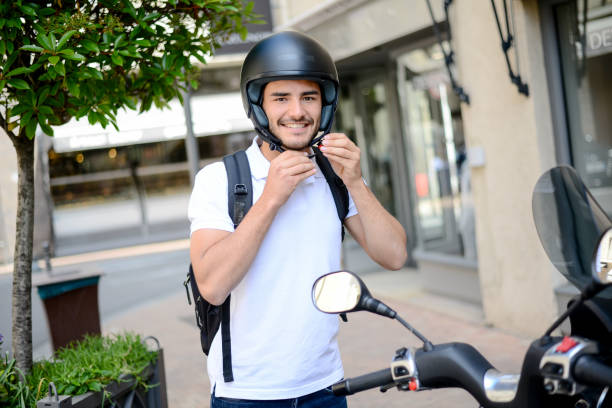 handsome young man in a modern city adjusting motorcycle helmet in summer - helmet motorbike imagens e fotografias de stock