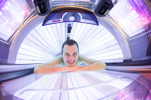 Handsome young man in a modern solarium Handsome young man relaxing during a tanning session in a modern solarium dark spots face stock pictures, royalty-free photos & images